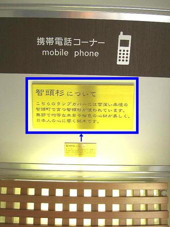 「携帯電話コーナー」内の照明器具の上にはランプカバーに使われている智頭杉の解説銘板が付けられている(解説銘板部分の拡大表示付き)