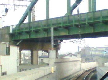 おおさか東線・JR俊徳道駅から久宝寺方向を望む。すぐ上に見える高架は近鉄大阪線のもので、写真画像に写っているトラス橋を右手方向に越えたところに近鉄の俊徳道駅がある《車内前面展望で;090613撮影》