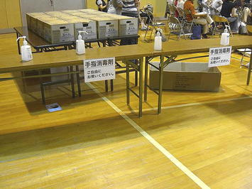 体育館内後方中央に設置された消毒液ボトルの置かれたテーブル。奥に見えるダンボール群の中にはレッスン終了後にクラス生一人一人に配られる500mlペット入り「天然水」が入っていた《090910撮影》