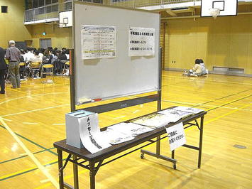 会場内後方に設置された連絡用ホワイトボードと配布物デスク。新たにメッセージ用紙投函ボックスが置かれていた