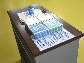 受付デスク横に設置された教壇机の上に陳列された販売品たち。パート毎の練習用CDと「第九」合唱スコア冊子が陳列されていた《091112撮影》