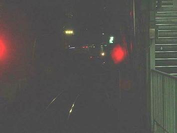 我が大阪環状線外回り電車を待避させて通過していった関空特急「はるか」(見えにくいかな…)。右隣には天王寺に向かう快速電車の前照灯などが見える《091126撮影》