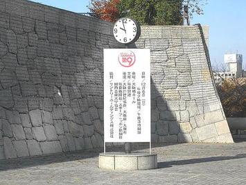 大阪城ホール北玄関右横に建植されているソーラー式時計と、そこに立てかけられた催事関係者一覧表示板。時計は門限2~3分前を指していた