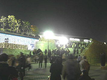 昔ながらの電球色に青色の2色の電飾が綺麗に光る中を家路などへ足を向ける合唱参加者たち。ホール北玄関に通ずる石階段横から《091206撮影》