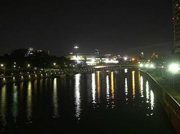 大阪環状線の線路の側に架けられた橋の上から見える、大阪城ホール北玄関全景。すぐ前に見える川の水面に映る光の数々との取り合わせが何とも言えぬ雰囲気を醸し出す《091206撮影》