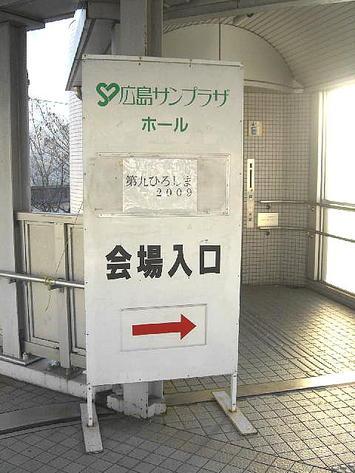歩道橋上のエレベータのりば前に立てかけられた、「第九ひろしま2009」と印刷された紙の貼られた広島サンプラザの看板《091219撮影》