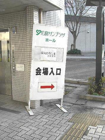 歩道橋下の歩道上のエレベータのりば前に立てかけられた、「第九ひろしま2009」と印刷された紙の貼られた広島サンプラザの看板《091219撮影》