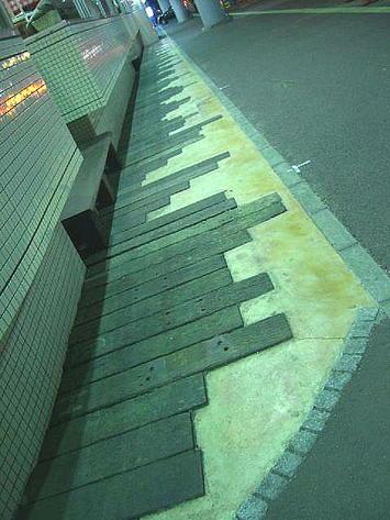 """広島サンプラザの道路を挟んで反対側に位置する商業施設「アルパーク」西棟の根元に見える""""枕木アート""""。アルパーク側から新井口駅側に向けての眺め。表面の感じなどから鉄道の枕木ではないかと直感していた《091220撮影》"""