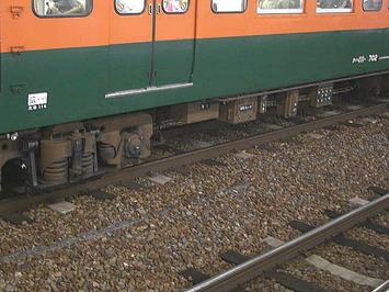 広島駅3番のりばに停車していた、湘南色の車両の車体側面下部の様子。乗務員室(運転台)すぐ横に見える所属先表示のところはクリーム色に塗りつぶされて「広ヒロ」と描かれ、中央部分に見える車番表示の製造番号表示部の頭の部分に1桁分の不自然な空白が…《091220撮影》