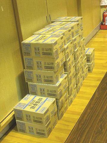 会場最後方の、舞台に向かって右手に積まれていたリニューアル版「鉄骨飲料」のケース(箱)。レッスン終了後にクラス生全員に配布された《100902撮影》