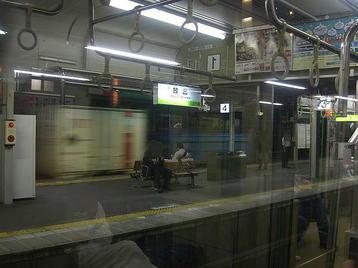 放出駅で発車を待つおおさか東線の電車の車窓から見える、隣のホーム(京橋方面ホーム)の奥側を通過する貨物列車。普通に撮影《101014撮影》