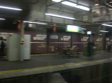 放出駅で発車を待つおおさか東線の電車の車窓から見える、隣のホーム(京橋方面ホーム)の奥側を通過する貨物列車。流し撮りにて《101014撮影》