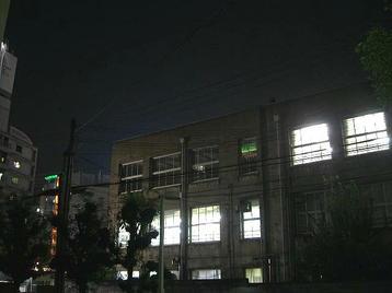 レッスン会場の梅田東学習ルーム体育館(特別研修室)の玄関から見える、道路を挟んで反対側に建つ同ルーム本館(旧校舎)とその左側に見える風景。体育館玄関から真正面に見える本館2階の窓は照明が灯されていなかった《11月11日撮影》