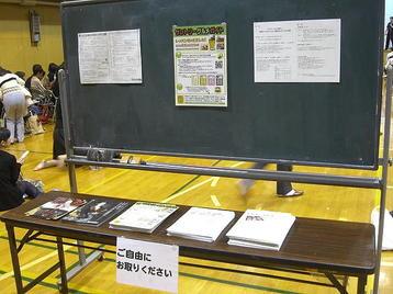 「大阪5」クラス・5回目レッスン当日の連絡ボード(黒板)と配布物デスクの様子。「第九ひろしま2010」合唱団員募集チラシの代わりに、「万九」本番当日に於ける昼食用仕出し弁当の予約受付案内チラシが置かれているのが見えた《11月11日撮影》