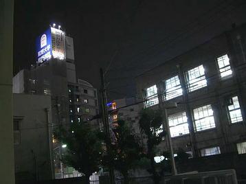 レッスン会場・梅田東学習ルーム体育館(特別研修室)の玄関から見える、同学習ルーム本館(旧校舎)とその左手に見える建物群。オレンジ色と青色の各照明が周囲の建物群に彩りを添えている《101125撮影》